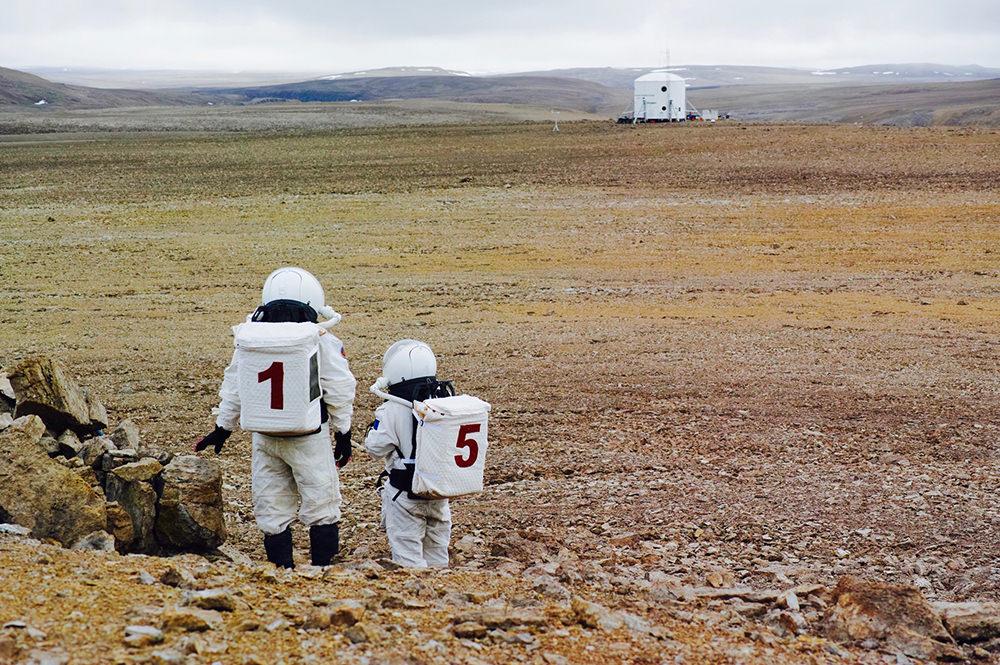 模擬宇宙服を着て、凍土の残る荒野を歩く人とシェルター