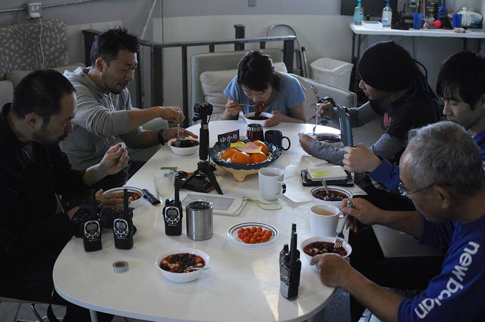 食卓を囲んでスープを食べる6人。食卓には手作りのスープやフルーツが並ぶ。
